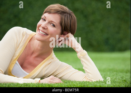Smiling Woman lying on grass Banque D'Images