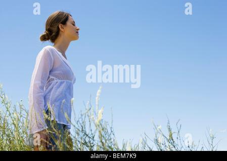 Jeune femme debout dans l'herbe haute, les yeux fermés, side view