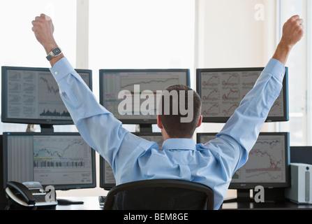 Négociant mâle raising arms dans la réussite