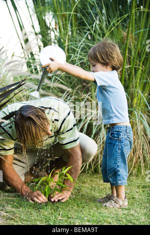 Petit garçon verser de l'eau sur la tête de son père comme il travaille dans le jardin Banque D'Images