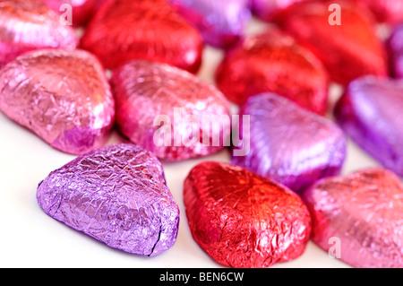 Saint Valentin chocolats enveloppés de papier aluminium rouge et violet sur fond blanc Banque D'Images