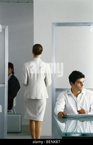 Female executive marche à travers bureau alors que ses collègues de travail, vue arrière