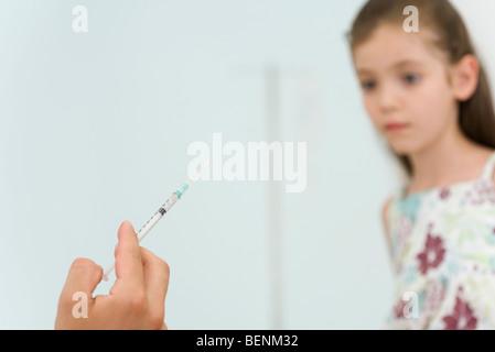 Doctor holding syringe, prépare à vacciner little girl, portrait