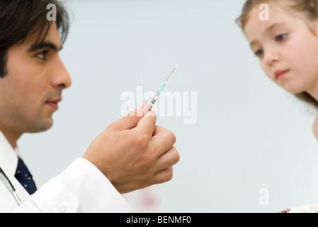 Pédiatre montrant petite seringue