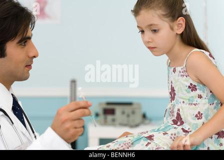 Pédiatre expliquant seringue pour petite fille