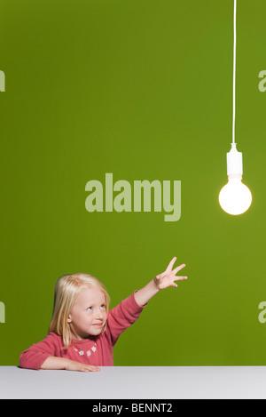 Petite fille pour atteindre l'ampoule lumineuse suspendue au-dessus Banque D'Images