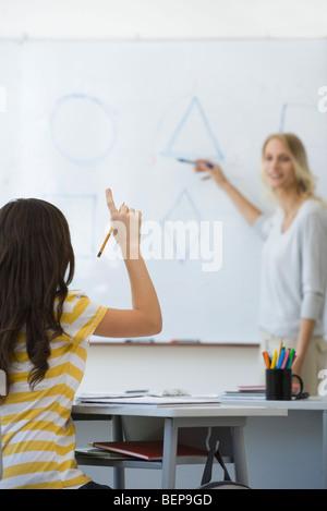 High school student raising hand, répondre aux questions de l'enseignant