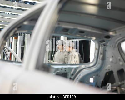 Les travailleurs des usines de voiture discussing work Banque D'Images