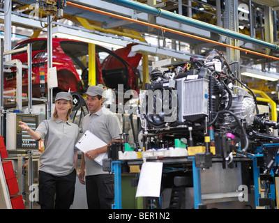 Location de travailleurs d'usine avec des pièces de voiture Banque D'Images