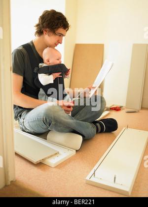 L'homme avec la fabrication de meubles de bébé Banque D'Images