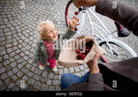 Petite fille veut avoir des cerises Banque D'Images