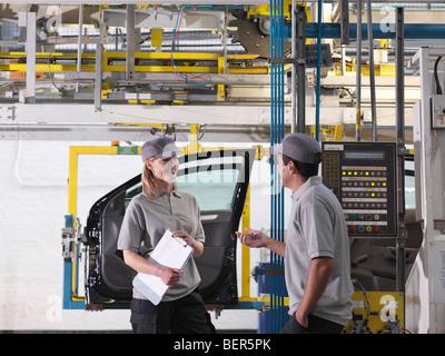 Location de travailleurs d'usine sur la ligne de production Banque D'Images