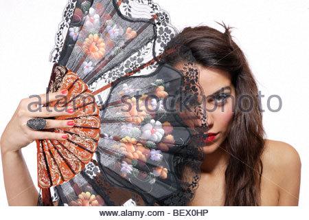 Une belle femme espagnole derrière ventilateur traditionnel sur fond blanc Banque D'Images