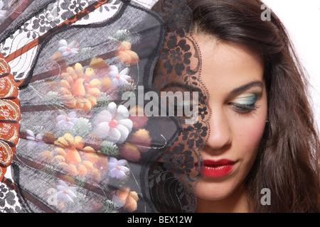 Une belle femme espagnole derrière ventilateur traditionnel sur fond blanc - l'accent sur la main Banque D'Images