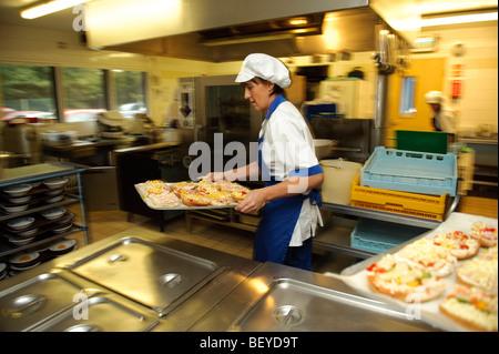 Femme cuisinier dans une cantine de l'école primaire à propos de cuisine pour cuire un bac de pizzas pour le déjeuner, Banque D'Images