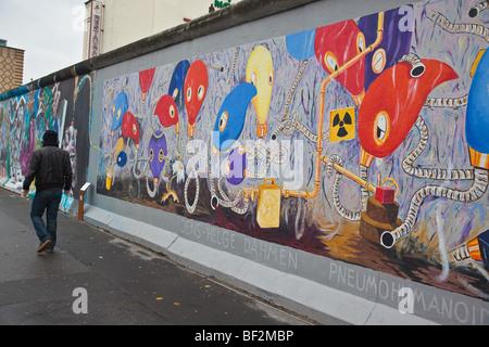 Repeint récemment fresque avec un homme en passant devant le Mur de Berlin à l'East Side Gallery à Berlin Kreuzberg Banque D'Images