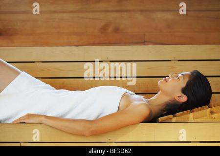 Asian woman relaxing in sauna