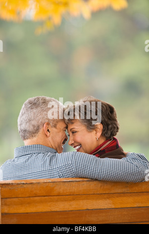 African couple hugging on park bench Banque D'Images