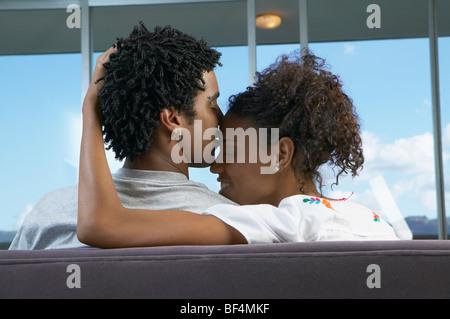 Vue arrière de l'African couple hugging on sofa Banque D'Images