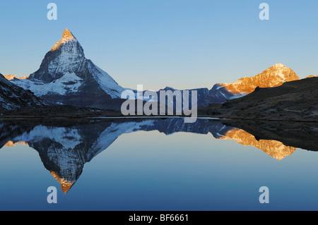 Matterhorn au lever du soleil en hiver avec reflet dans l', Riffelsee Zermatt, Valais, Suisse, Europe Banque D'Images