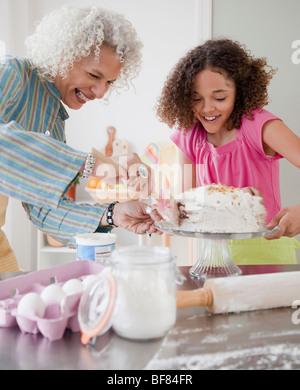 Grand-mère et petite-fille frosting cake Banque D'Images