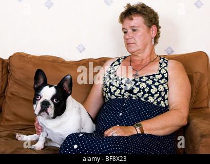 Femme assise avec découragement et dépression pitbull dog sur la table SerieCVS517505 Banque D'Images