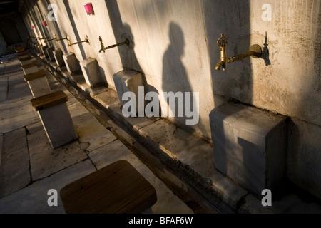 Laver le visage avant de prier l'homme à l'extérieur de la mosquée bleue à Istanbul Banque D'Images