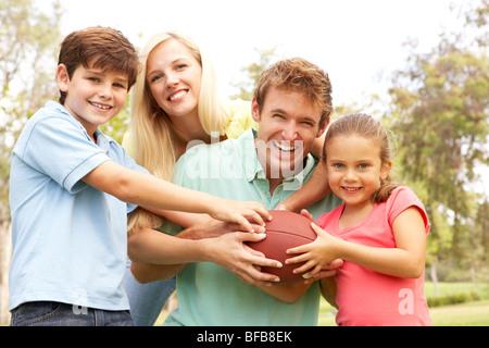 Famille au football ensemble dans Park Banque D'Images