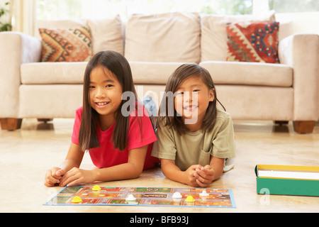 Deux jeunes filles, jouant à la maison du jeu de société Banque D'Images