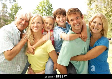 La mère et le Père donne aux enfants Piggy Back avec les grands-parents Banque D'Images