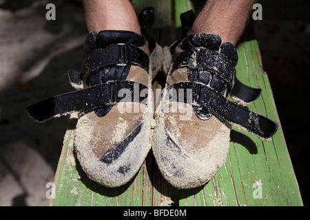 Un homme couvert de chaussures du grimpeur dans le sable après le bloc sur la plage dans les Caraïbes. Banque D'Images