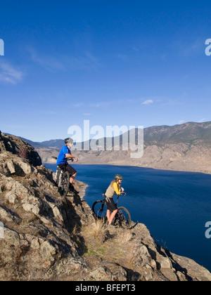 Jeune couple enjoying view de Kamloops Lake tout en vélo de montagne sur une belle journée à l'ouest de Kamloops Banque D'Images