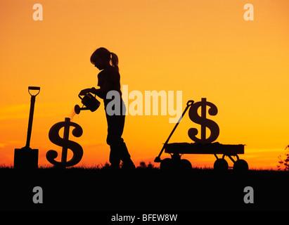 Cadre conceptuel d'une jeune fille d'arroser un signe dollar nouvellement plantés près de Winnipeg, Manitoba, Canada Banque D'Images