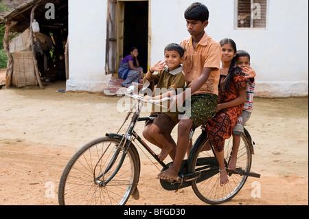 Les enfants et adolescents indiens de rouler à vélo dans un village de l'Inde rurale. L'Andhra Pradesh, Inde Banque D'Images