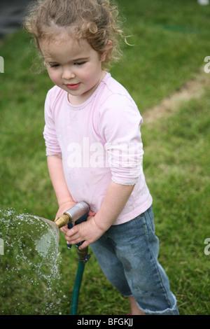 Little girl holding un tuyau de jardin Banque D'Images