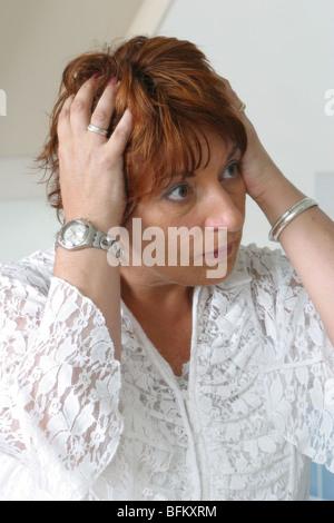 Confondu ahuri woman touching tête ou cheveux - Un seul Banque D'Images