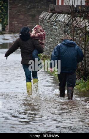 Famille pataugeant dans l'eau d'inondation à Eamont Bridge, Cumbria Banque D'Images