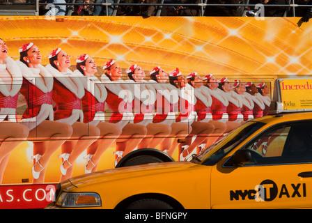 Taxi passe un tour bus avec une publicité pour la Radio City Music Hall Christmas Spectacular avec les Rockettes Banque D'Images