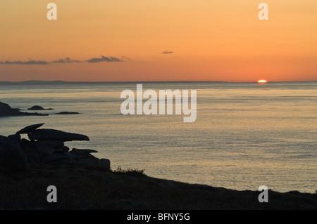 Dawn soleil montant de la mer au large des îles Scilly sur St Marys, avec Pulpit Rock vers la gauche.