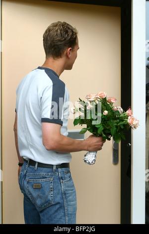 L'homme habillé décontracté avec bouquet de fleurs at front door Banque D'Images