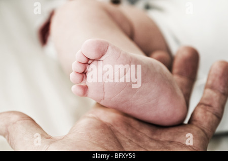 Bébés pied dans la paume de la main du parent Banque D'Images