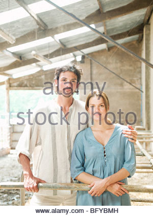 Man and Woman standing in cattle shed Banque D'Images