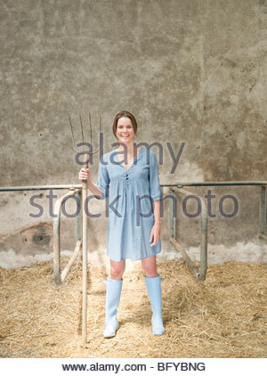 Femme avec fourche en étable Banque D'Images