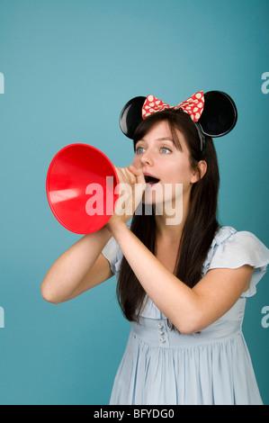 Femme portant des oreilles de souris et de crier dans un mégaphone