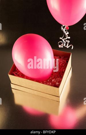Boîte en carton avec des ballons parti rose Banque D'Images