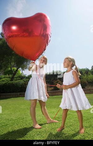 Les jeunes filles tenant ballon coeur rouge Banque D'Images