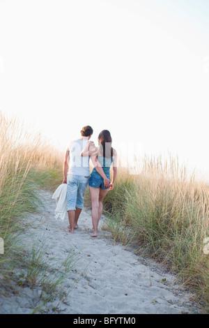 Couple strolling along beach Banque D'Images