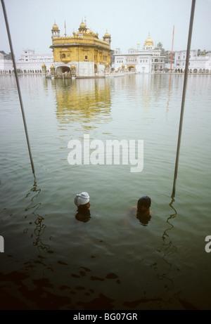 Deux pèlerins Sikhs se baignent dans l'eau entourant le temple d'or, connu sous le nom de Harmandir Sahib et considéré Banque D'Images