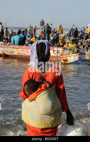 Le déchargement des bateaux de pêche (pirogues), Marché aux poissons de Mbour, Mbour, Sénégal, Afrique de l'Ouest, Banque D'Images