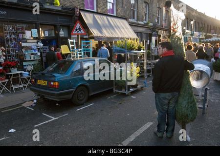 Un homme qui a acheté un arbre de Noël à Columbia Road Flower Market à Londres Banque D'Images